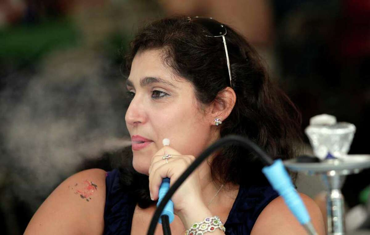Rita Jowdy, of Brookfield, smokes tabacco from an Arkele during the Lebanese Heritage Festival at St. Anthony Maronite Church in Danbury August 13, 2010.