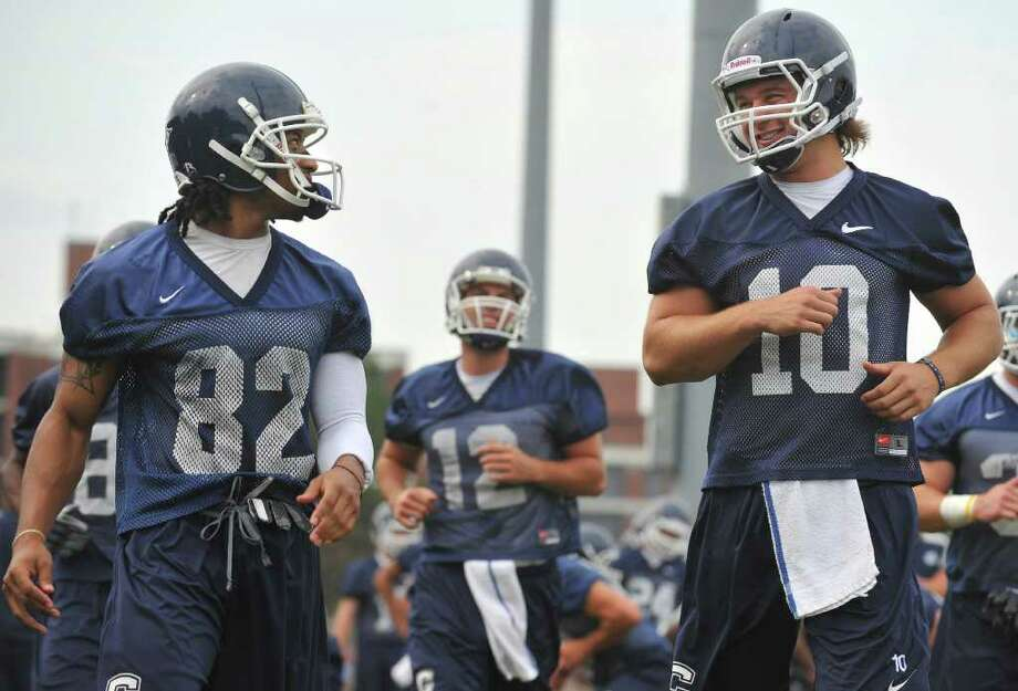 Connecticut's Kashif Moore, left, and Zach Frazer, right, talk after a drill during football practice at Storrs, Conn., Monday, Aug. 9, 2010.  (AP Photo/Jessica Hill) Photo: AP