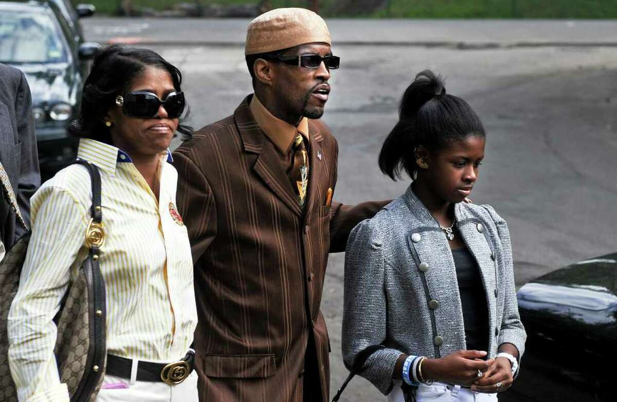 Former State Sen. Ernest E. Newton II approaches the Chase Center, a halfway house in Waterbury where he finished out his sentence for federal corruption charges, to sign himself out of the facility Friday August 13, 2010. Newton is flanked by his sister Patricia Newton-Foster and thirteen-year-old daughter Kayla.
