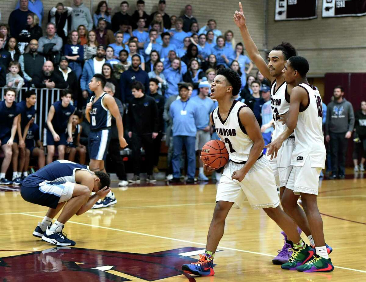Windsor, Connecticut - January 28, 2020: Matt Knowling of East Catholic H.S. holds his hands to his head in defeat, left, as Corey McKeithan of Windsor H.S, second from left, and teammates Justice Ellison, third from left, and Shomar Leaphart celebrate their win over East Catholic H.S. during boys basketball Tuesday evening at Windsor. Final: #2 Windsor H.S. defeats #1 East Catholic H.S. 48-45.