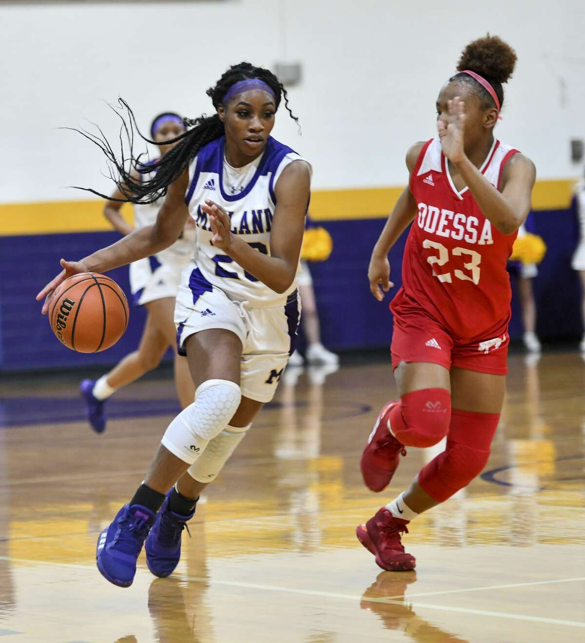 Midland High's Kobe Powell dribbles the ball down the court as Odessa High's Kazyiah Hicks (23) guards her Tuesday, Jan. 28, 2020 at Midland High School.