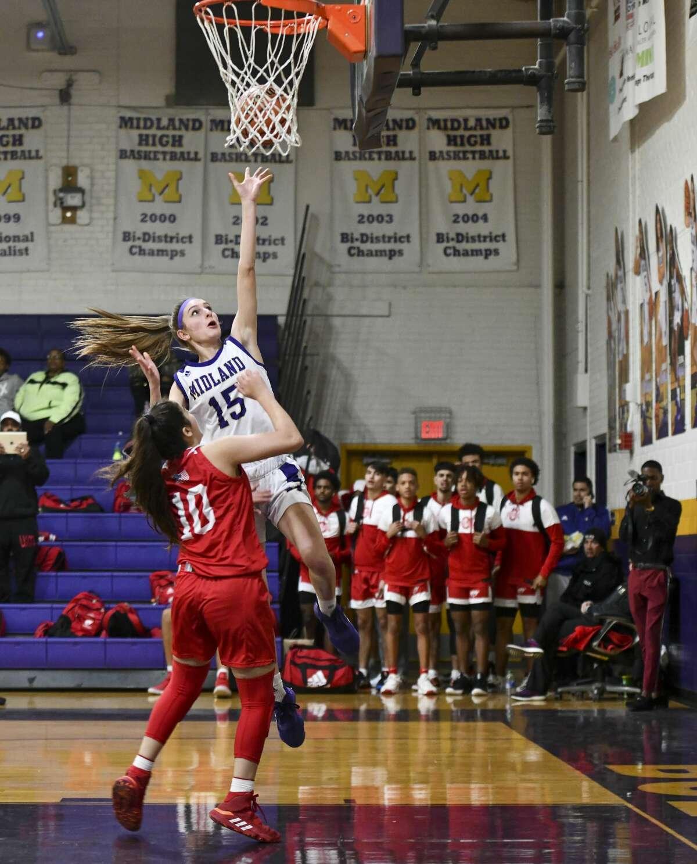 Midland High's Sam Braudaway (15) scores against Odessa High's Nevaeh Carrasco (10) on Tuesday, Jan. 28, 2020 at Midland High School.