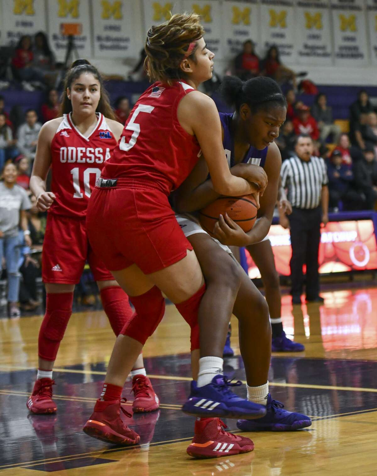 Midland High's Ty'Eisha Satterwhite and Odessa High's Amber Escantrias battle for the ball Tuesday, Jan. 28, 2020 at Midland High School.