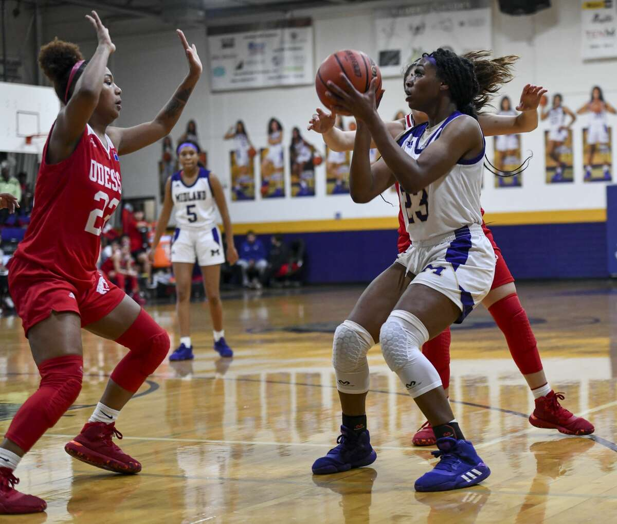 Midland High's Kobe Powell (23) shoots the ball Odessa High's Kazyiah Hicks comes from the basket to attempt to guard Powell on Tuesday, Jan. 28, 2020 at Midland High School.