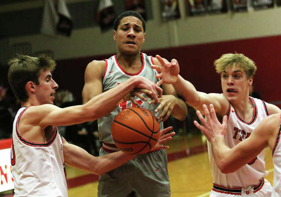 Alton's Dante' Herrin (middle) draws a foul while going up for a shot between Chatham Glenwood's Tyler Estes (left) and Eli Vogler in the first quarter Tuesday night in Chatham. Photo: Greg Shashack | The Telegraph