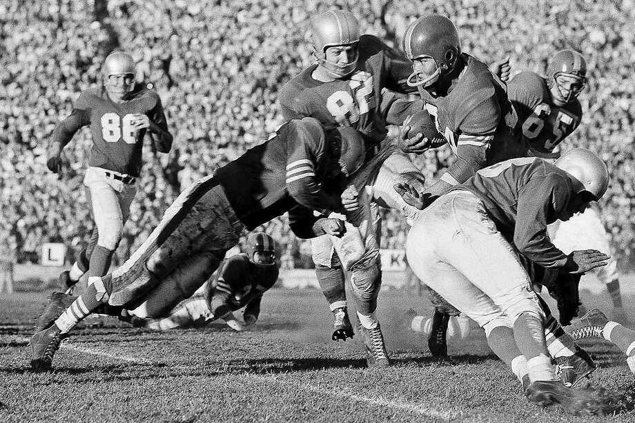49ers fullback Joe Perry breaks through the Detroit Lions line for 14 yards with help from teammate Leon Hart (82) on Oct. 31, 1955. Photo: Ray Howard / Associated Press 1955