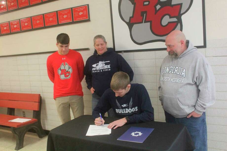 Reed City's Calvin Rohde signs his letter of intent with Concordia University of Nebraska on Thursday, surrounded by his parents, Grant and Laura Rohde, and his brother, Aaron Rohde. (Herald Review photo/John Raffel)
