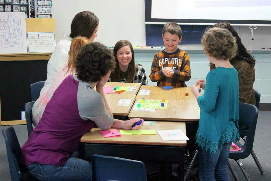 Families learn a fun game to help tune their first graders' math skills in Michaela MacGirr's classroom. (Photo/Robert Myers)