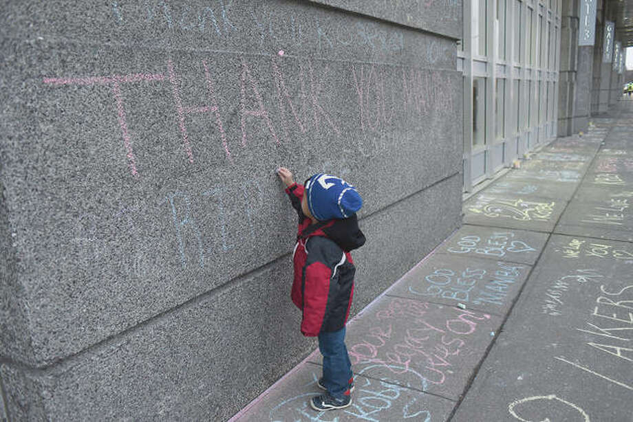A child writes on a wall outside the United Center honoring Kobe Bryant before an NBA basketball game between the Chicago Bulls and the San Antonio Spurs in Chicago.