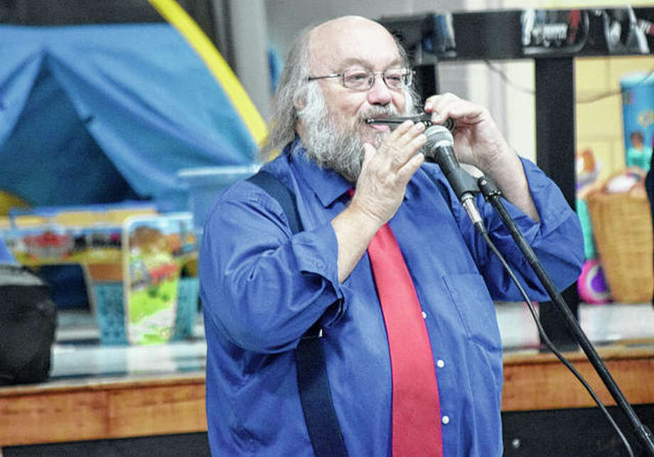 Jacksonville performer Mike Anderson plays a jaw harp during Murrayville-Woodson Elementary School's Camp Read-a-Lot Family Night on Tuesday. Photo: Marco Cartolano | Journal-Courier