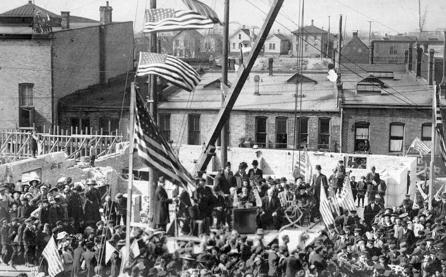 A large crowd gathers for the ground breaking ceremony of the new post office building on Maple Street in this early 1900 photograph. The building that was constructed is the current home to the Manistee City Hall.