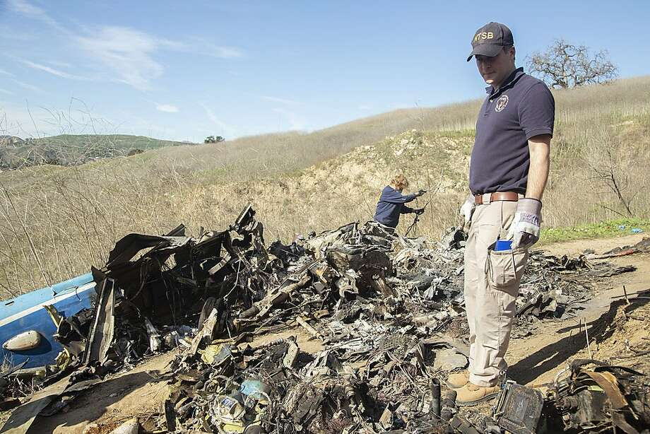 In this image taken Monday, Jan. 27, 2020, and provided by the National Transportation Safety Board, NTSB investigators Adam Huray, right, and Carol Hogan examine wreckage as part of the NTSB's investigation of a helicopter crash near Calabasas, Calif. The Sunday, Jan. 26 crash killed former NBA basketball player Kobe Bryant, his 13-year-old daughter, Gianna, and seven others (James Anderson/National Transportation Safety Board via AP) Photo: James Anderson, Associated Press