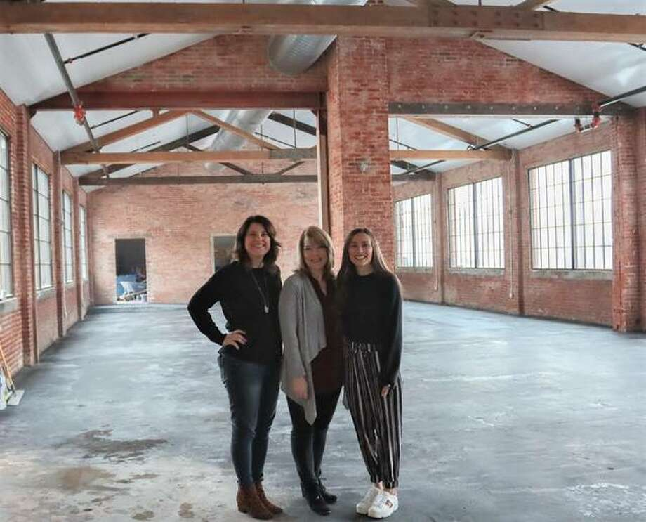"""The Ink House Event Center owners, Kristen Pfund, left, of Edwardsville, and Hannah Fink, right, of Glen Carbon, stand with Restore Décor Executive Director Dana Adams, of Edwardsville, in The Ink House's main space, named The Headliner. The new downtown venue is located in the former home of The Intelligencer and will host its first event — Restore Décor's third annual fundraiser, """"Heart for Our Community"""" — Saturday, Feb. 1. Photo: For The Intelligencer"""