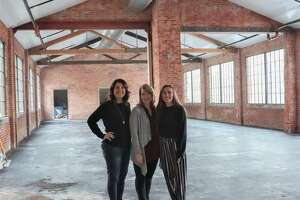 """The Ink House Event Center owners, Kristen Pfund, left, of Edwardsville, and Hannah Fink, right, of Glen Carbon, stand with Restore Décor Executive Director Dana Adams, of Edwardsville, in The Ink House's main space, named The Headliner. The new downtown venue is located in the former home of The Intelligencer and will host its first event — Restore Décor's third annual fundraiser, """"Heart for Our Community"""" — Saturday, Feb. 1."""