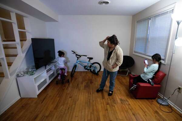 Tania Rodriguez, 48, with her daughters Charlotte and Caroline in their new West Haven home.
