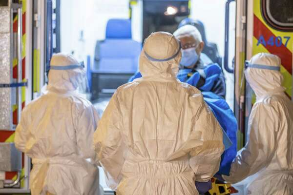 Medical workers in protective gear transport a patient believed to be a confirmed case of the Wuhan coronavirus, also known as 2019-nCoV, at Queen Mary Hospital in Hong Kong on Jan. 29, 2020.