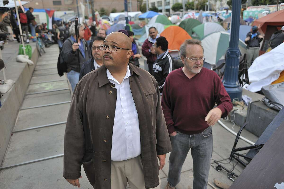 Mohammed Nuru, left, Interim Director of the San Francisco Department of Public Works walks the Occupy SF camp at Justin Herman Plaza with Richard Kriedler, an Occupy representative as they try to coordinate plans to allow people to stay at the plaza without violoating laws or creating unsafe conditions.