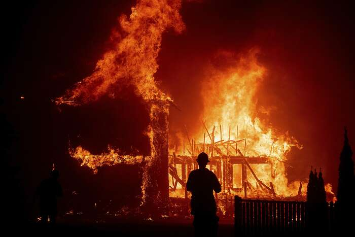 FILE - In this Thursday, Nov. 8, 2018 file photo, a home burns as the Camp Fire rages through Paradise, Calif. California Gov. Gavin Newsom wants to hire more state firefighters and make low-income communities safer from devastating wildfires in the budget he will send to state lawmakers on Friday, Jan. 10, 2020. (AP Photo/Noah Berger, File)