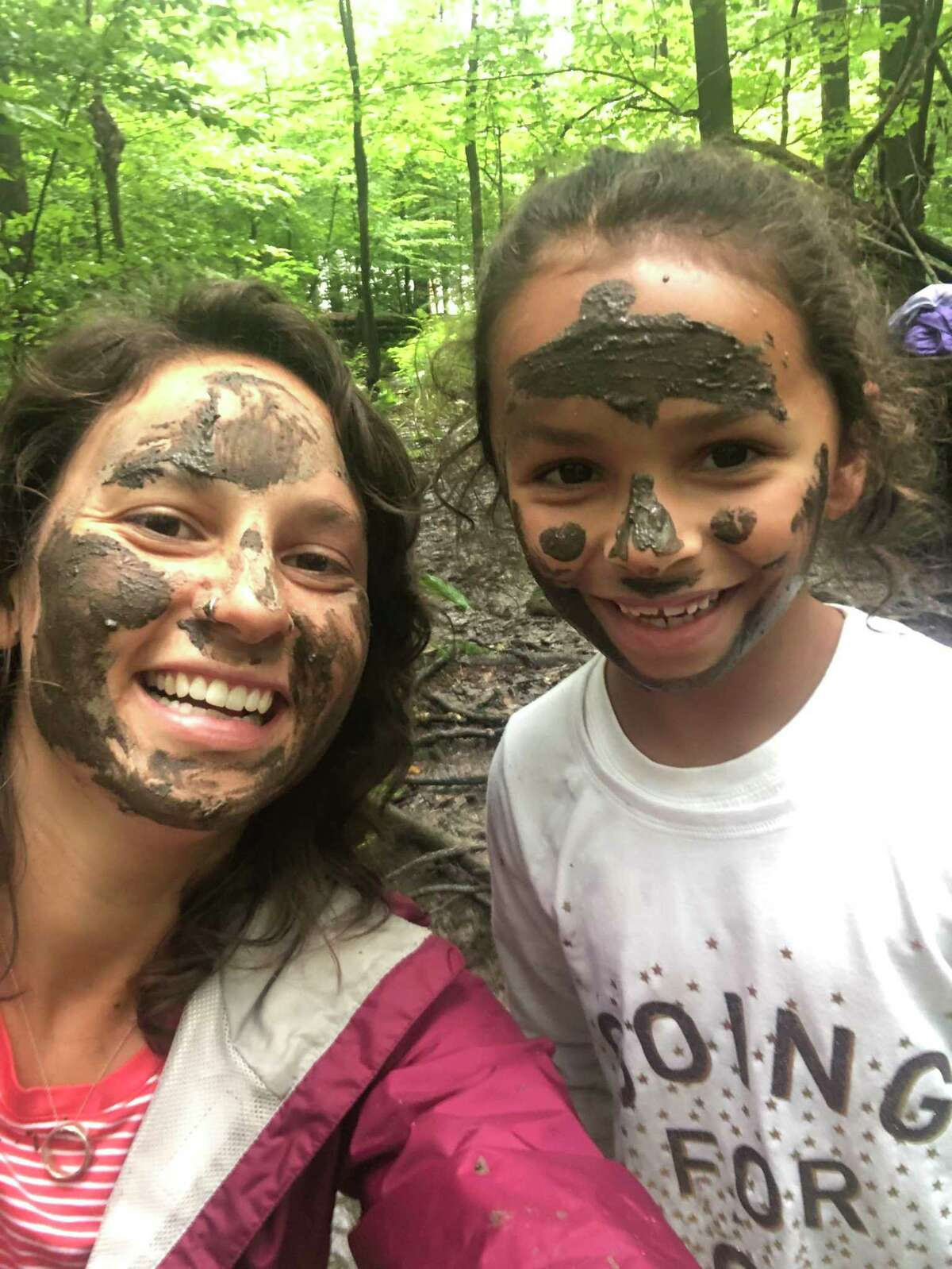Summer Camp director Victoria Heyne and a camper in mud masks.
