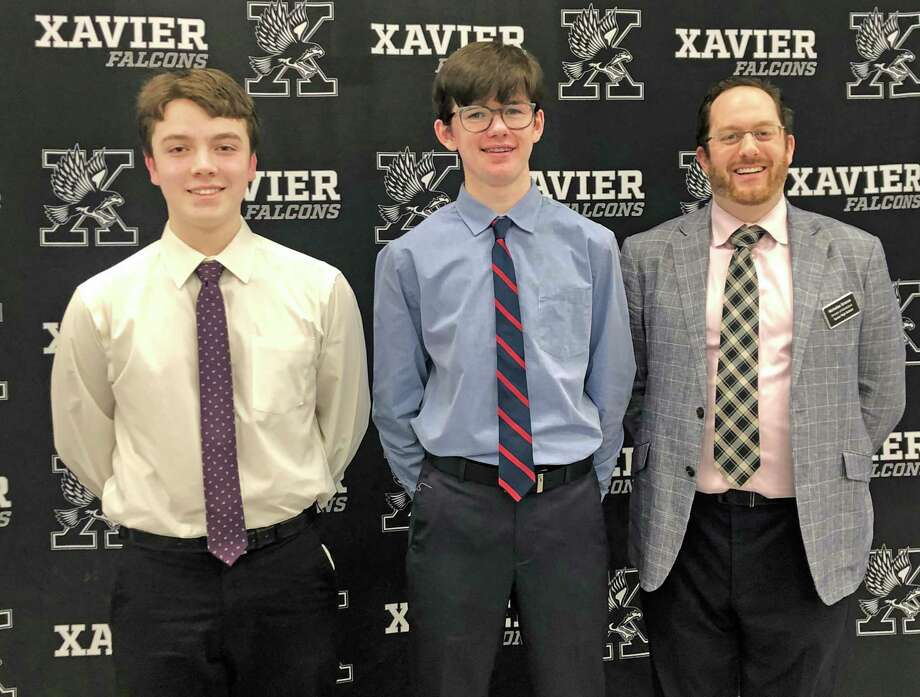 Old Saybrook St. John School eighth-grade students Ryan Coffey and Juan Pacheco-O'Donnell attained the top and second place scores on Middletown's Xavier High School entrance exam this year. They are shown with Xavier Director of Admissions Nicholas Grasso, right. Photo: Contributed Photo