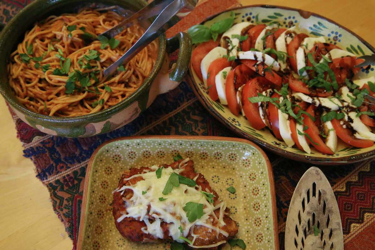 Chicken Parmesan becomes a whole Italian meal with spaghetti and a caprese salad at Jon Hinojosa's house.