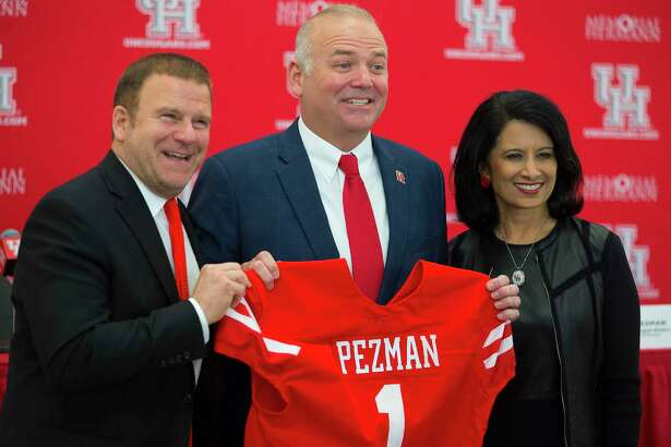 University of Houston board chairman Tilman Fertitta (left) and university chancellor Renu Khator (right) pose for photos with new athletic director Chris Pezman following an introductory press conference at TDECU Stadium, Tuesday, Dec. 12, 2017, in Houston.