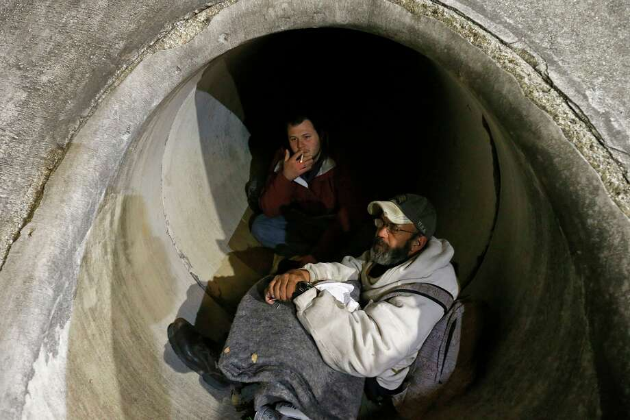 Phillip Kenowitz, left, and Marv Mitchel talk about being homeless while trying to stay warm in a drainage tunnel in this 2018 photo. Photo: Staff File Photo / © 2018 San Antonio Express-News