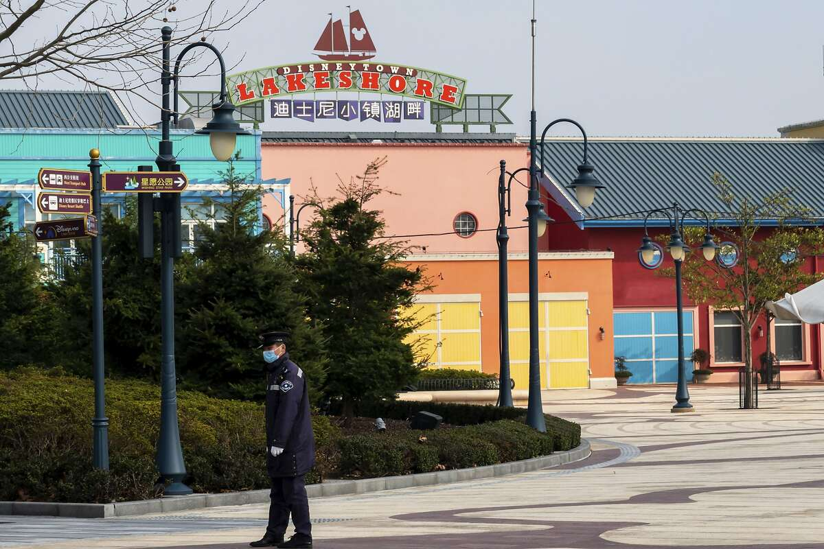 A security officer patrols at the closed Shanghai Disney Resort in Shanghai, Wednesday, Jan. 29, 2020. China as of Wednesday has more infections of a new virus than it did in with SARS, though the death toll is still lower. (Chinatopix via AP)