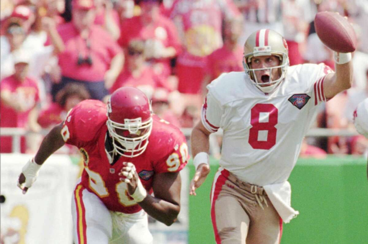 San Francisco 49ers quarterback Steve Young races ahead with the ball while chased by Kansas City Chiefs defensive end Neil Smith during the third quarter, Sunday, Sept. 11, 1994, in Kansas City, Mo. Young picked up 10 yards on the play. The Chiefs beat the 49ers 24-17. (AP Photo/John Sleezer)