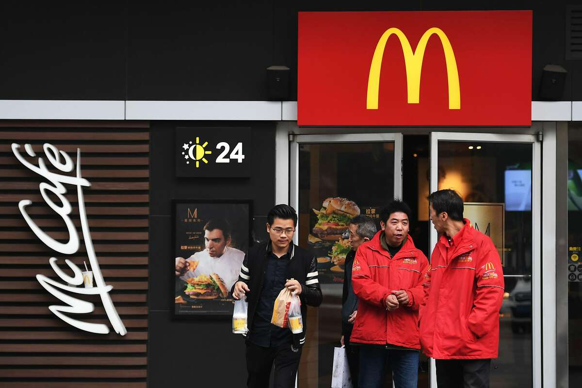 (FILES) In this file photo taken on October 26, 2017 people stand outside a McDonald's restaurant in Beijing. - US fast food giant McDonald's said on January 29, 2020 it closed all of its restaurants in Hubei, the Chinese province at the epicenter of a virus outbreak that has spread beyond the country's borders. The novel coronavirus outbreak traced to the provincial capital Wuhan in central China has killed more than 130 people and infected nearly 6,000 people across the country. (Photo by GREG BAKER / AFP) (Photo by GREG BAKER/AFP via Getty Images)