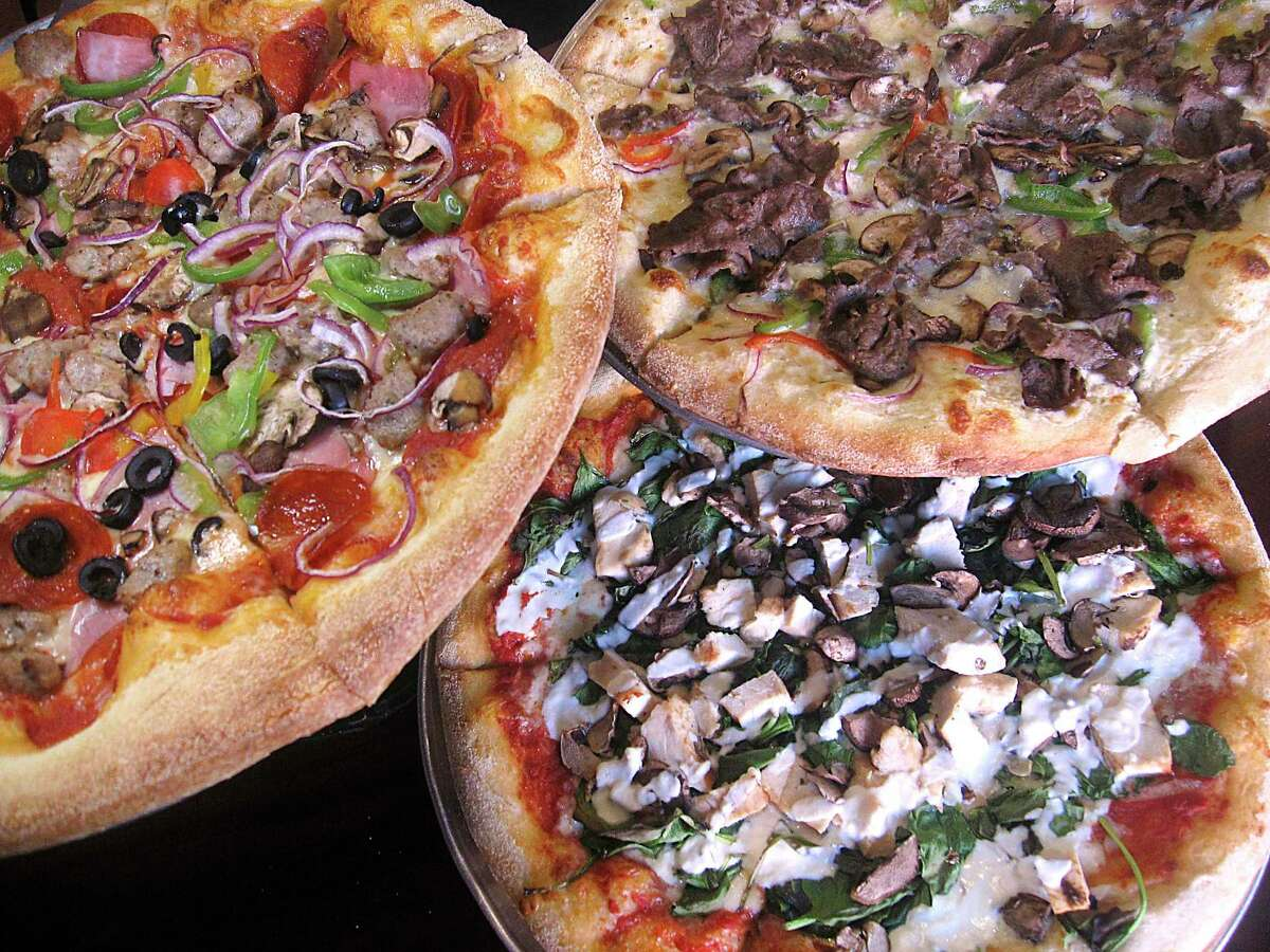 Pizza options include, clockwise from left, the Supreme, a Philly cheesesteak and Sofi's Pie with chicken and spinach at Sofia's Pizzeria.