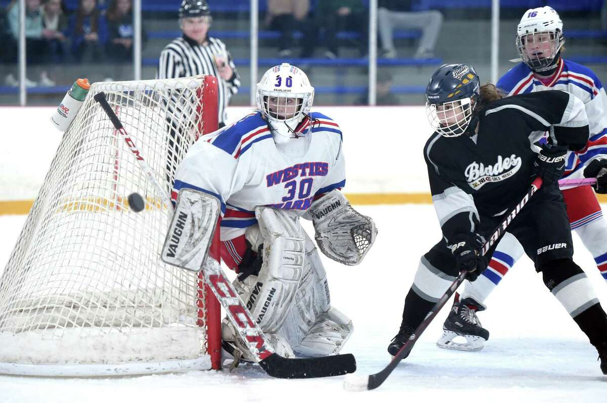 West Haven/Sacred Heart Academy goalie Kyleen Crowe defends against Tess Csejka (right) of the Amity/North Haven/Cheshire Blades in the SCC South Division Championship at Bennett Rink in West Haven on February 22, 2019.