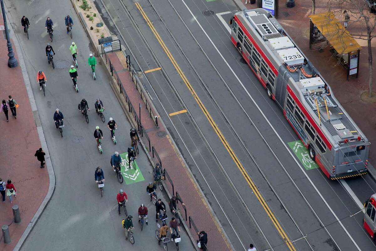 A group of cyclists with the San Francisco Bicycle Coalition ride in mass down Market Street in San Francisco, Calif. Wednesday, January 29, 2020. Beginning January 29, private vehicles will be banned from driving along Market Street between Steuart and 10th streets, leaving it free for cyclists, pedestrians and public transit vehicles.