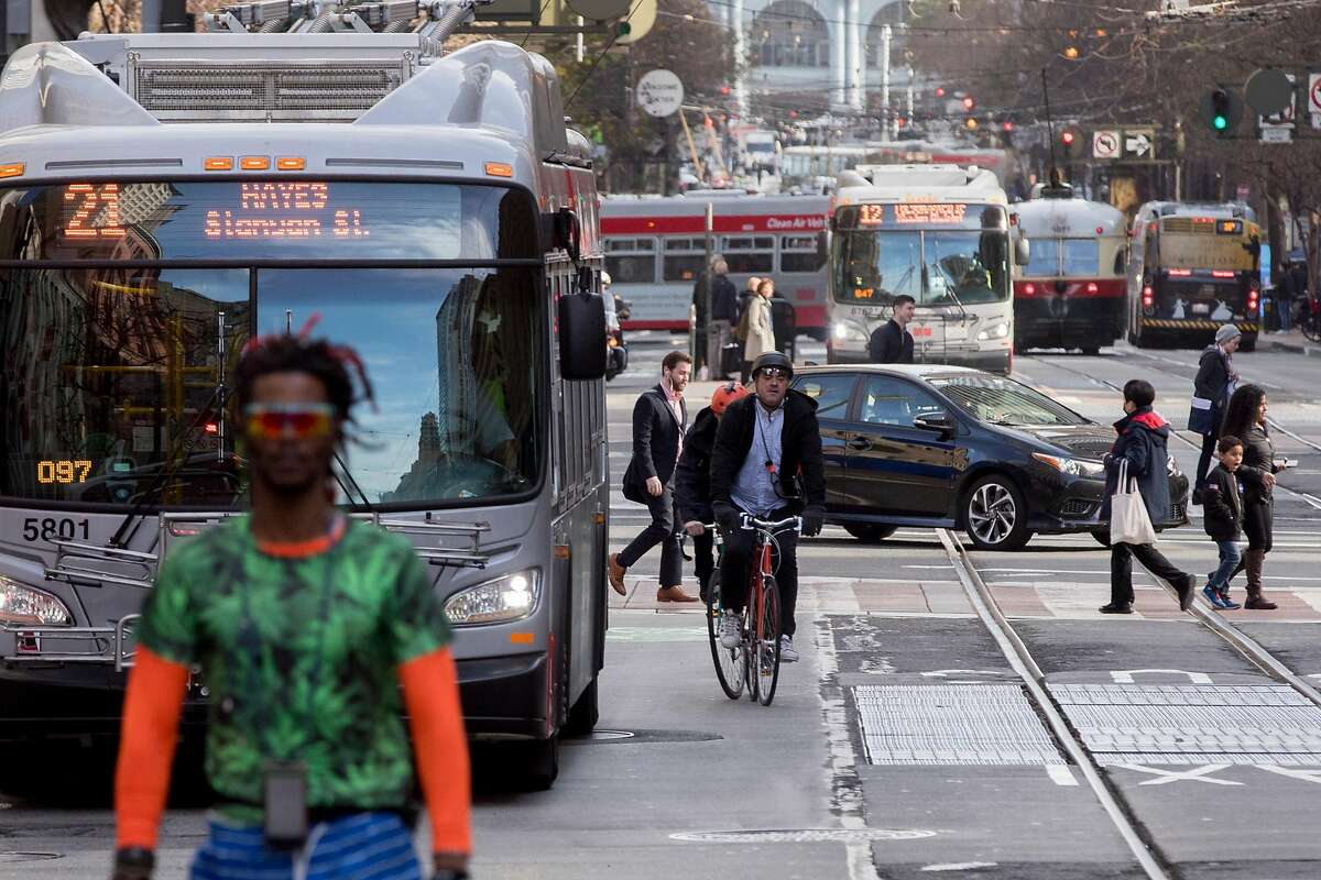 A mix of cyclists, buses and pedestrians move past one another on Market Street near Montgomery in San Francisco, Calif. Wednesday, January 29, 2020. Beginning January 29, private vehicles will be banned from driving along Market Street between Steuart and 10th streets, leaving it free for cyclists, pedestrians and public transit vehicles.