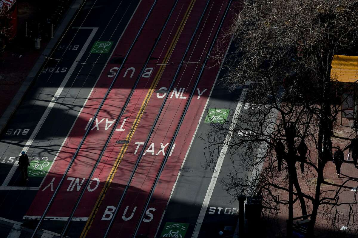 The light reflects bus and taxi only lanes painted on Market Street in San Francisco, Calif. Wednesday, January 29, 2020. Beginning January 29, private vehicles will be banned from driving along Market Street between Steuart and 10th streets, leaving it free for cyclists, pedestrians and public transit vehicles.