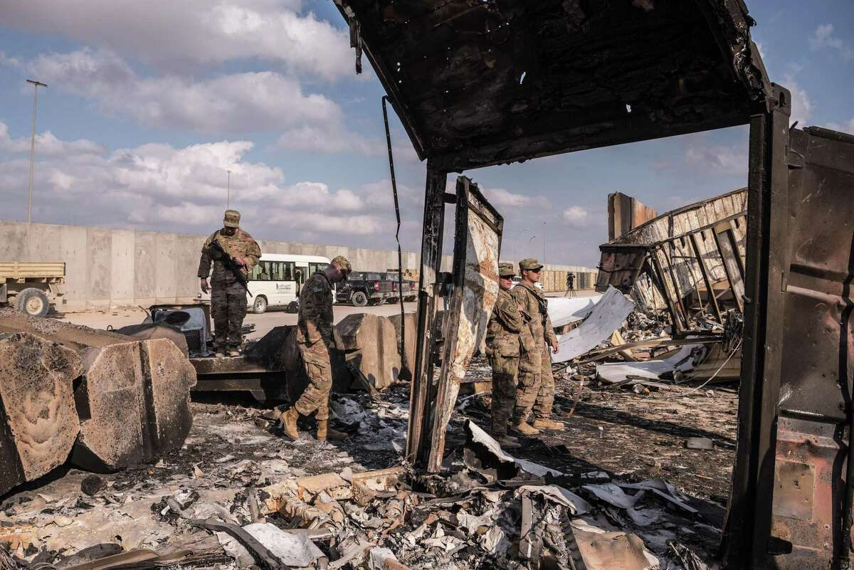 U.S. military personnel look at damage to a building at Al Asad Air Base in Anbar Province, west of Baghdad on Jan. 13, 2020. The Defense Department now says that 34 American service members have traumatic brain injuries from Iranian airstrikes on the base, contradicting President Donald Trump's dismissal of injuries earlier this week. (Sergey Ponomarev/The New York Times)
