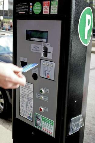 A driver pays at a parking meter payment machine in the    296165