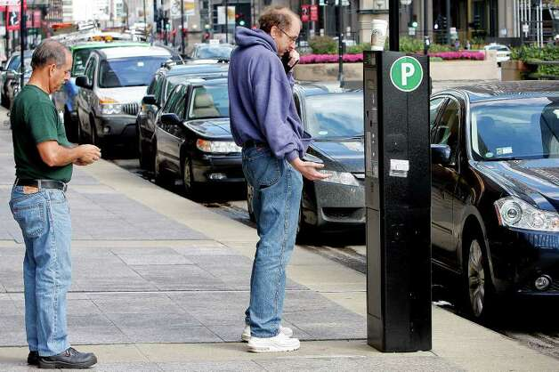 A driver pays for parking in the central business district