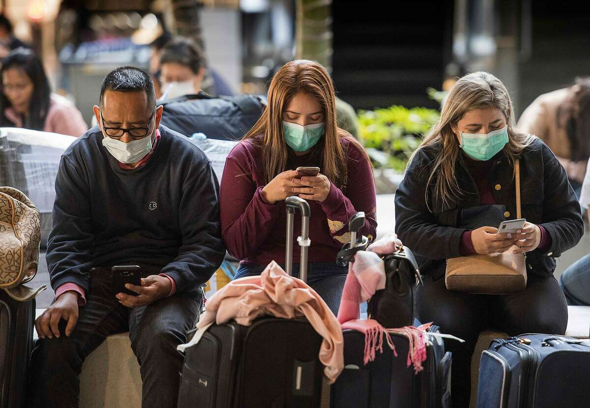 Passengers wear face masks as they arrive on a flight from Asia at Los Angeles International Airport on January 29, 2020.