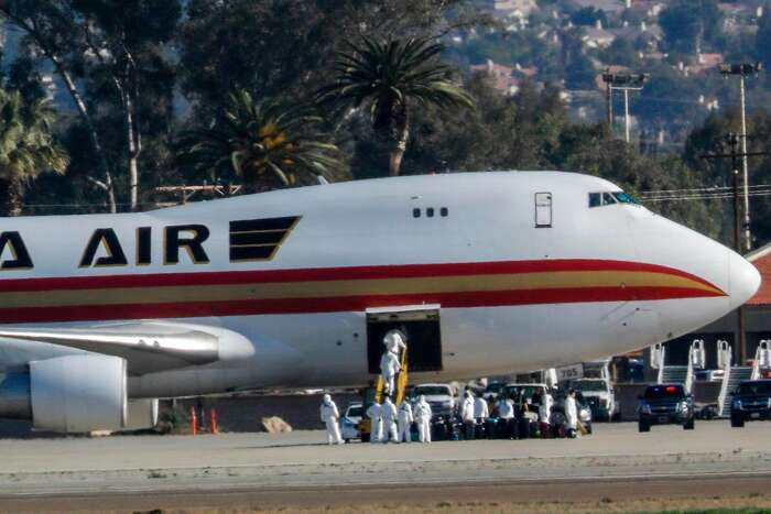 Men in white hazmat suits handle the luggage of about 200 American evacuees from Wuhan, China, after the plane landed at March Air Reserve Base on Wednesday, Jan. 29, 2020, in Riverside, Calif. The flight, chartered by the U.S. State Department, left the Chinese city of Wuhan and touched down late Tuesday night at Ted Stevens Anchorage International Airport in Alaska. After refueling and passenger screenings in Anchorage, it left for the March Air Reserve Base. (Irfan Khan/Los Angeles Times/TNS)