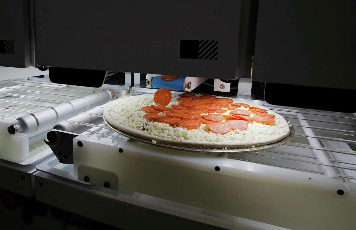Picnic's pizza-making robot makes a pizza at a food vendor's booth during the CES tech show in Las Vegas.