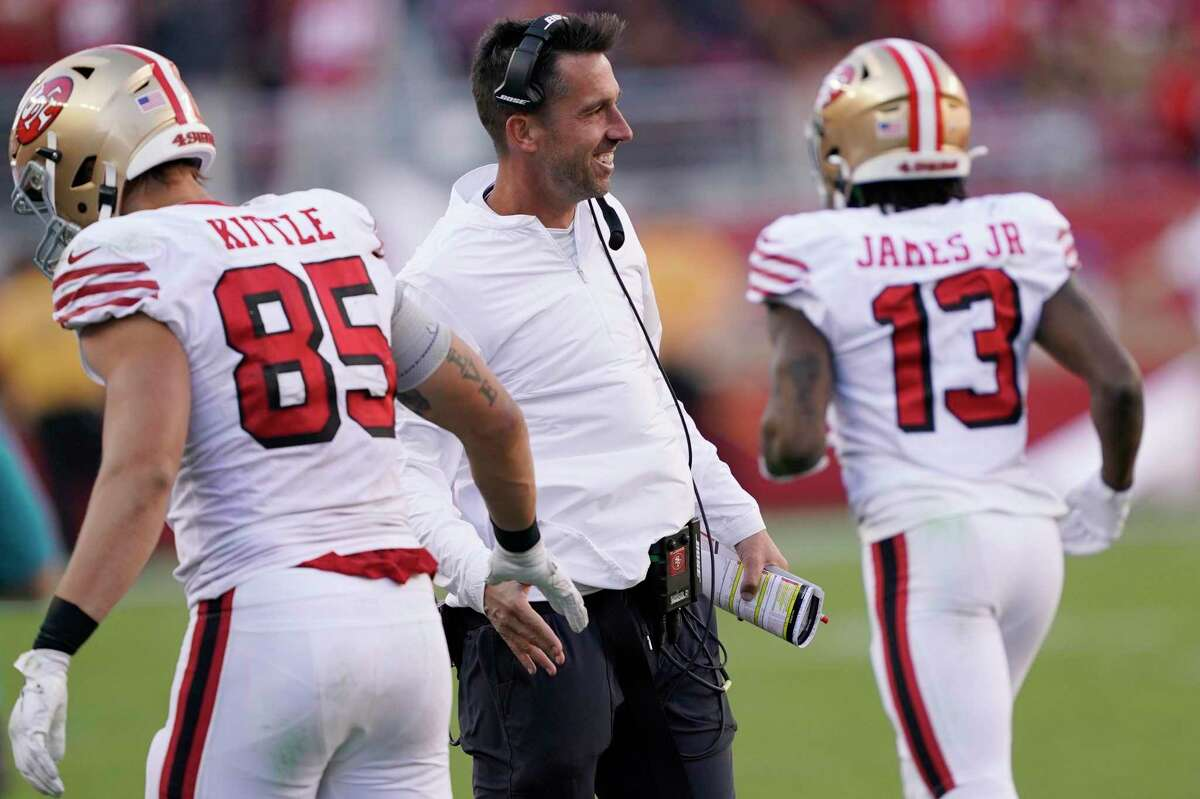 San Francisco 49ers head coach Kyle Shanahan greets tight end George Kittle (85) during the second half of an NFL football game against the Carolina Panthers in Santa Clara, Calif., Sunday, Oct. 27, 2019. San Francisco won the game 51-13. At right is San Francisco 49ers wide receiver Richie James (13). (AP Photo/Tony Avelar)