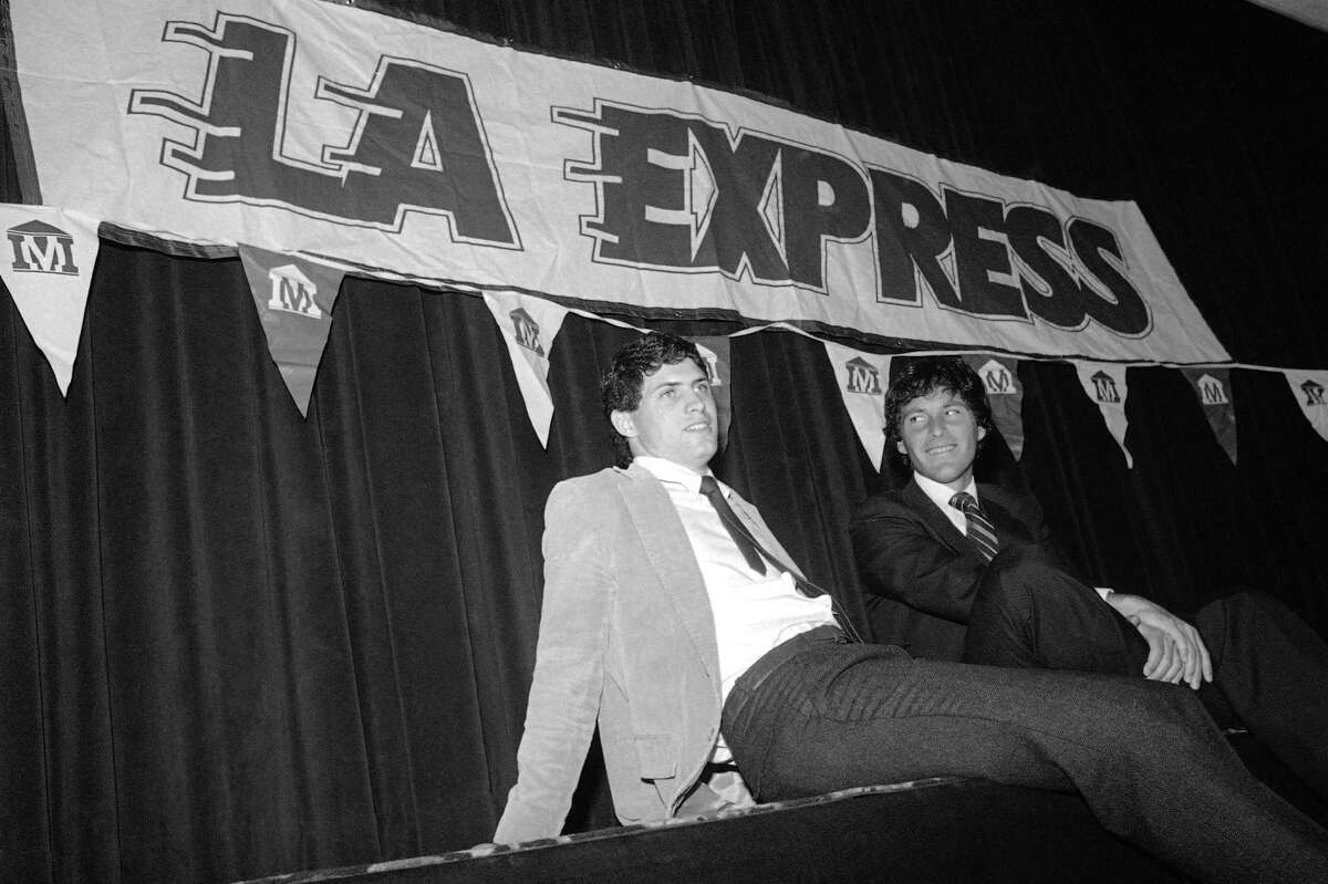 Brigham Young University quarterback Steve Young, with his attorney Leigh Steinberg, sits back after signing a $40 million over 43 years contract with the United States Football League's Los Angeles Express, March 6, 1984 in Los Angeles. (AP Photo/Doug Pizac)