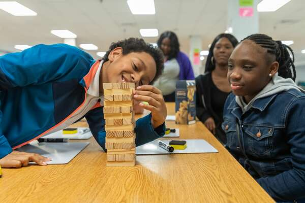 Sixth-graders Durell Smith, 11, and Byre-Anna Jones, 12, engage in a game of Math Jenga designed by their math teacher Courtney Booker. The math department at Willie Ray Smith Magnet Middle School held a STAAR Math night on Wednesday, January 29, 2020 to prepare their scholars for the upcoming STAAR Math test. Fran Ruchalski/The Enterprise