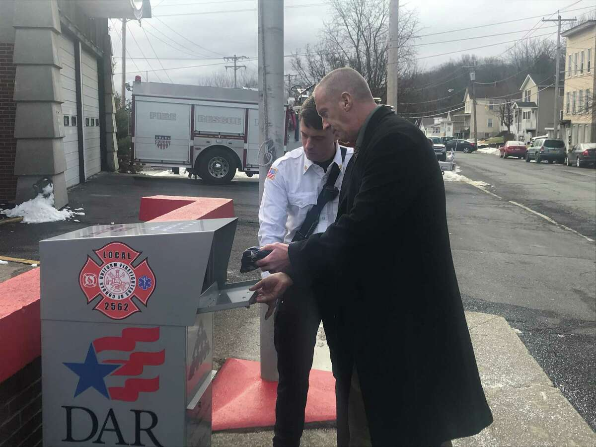 Cohoes Fire Department Lt. Russ Coonradt and Mayor Bill Keeler put an old American flag in the flag repository box sponsored by the city, the Uniformed Firefighters of Cohoes, the Daughters of the American Revolution and NH Kelman Recycling on Tuesday Jan 28, 2019 outside the Central Fire Station on Central Avenue in Cohoes, N.Y.A A The box is to allow the proper disposal of American flags (Kenneth C. Crowe II/Times Union)