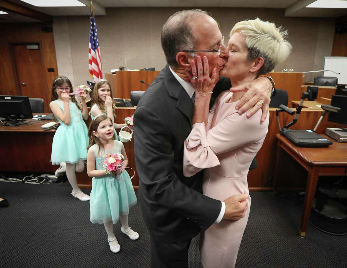 Macy, 10, Selah, 8, and Kate George, 5, from left to right, look in amazement as their grandfather former U.S. Attorney Ken Magidson his new wife Laura Kohlmaier kiss after being married by U.S. District Judge David Hittner Wednesday, Jan. 29, 2020, in Houston.
