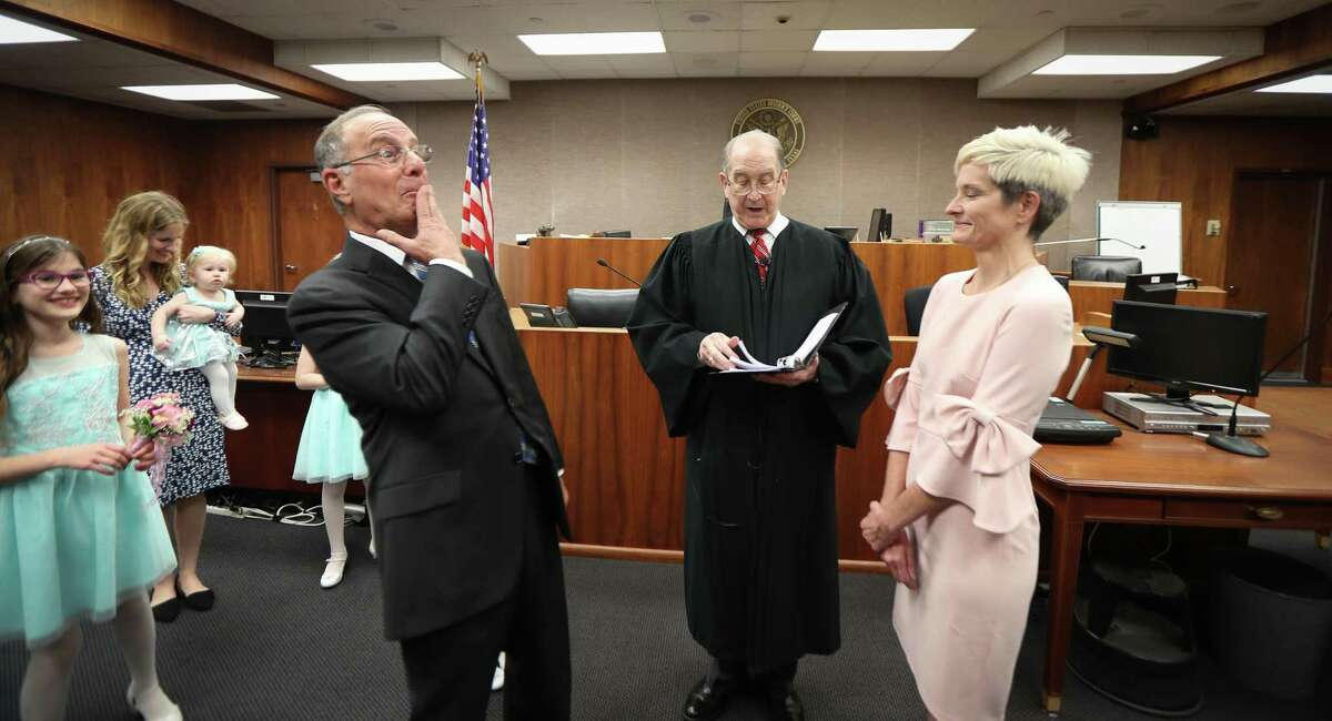 Former U.S. Attorney Ken Magidson covers his mouth after speaking his vow too soon as he and Laura Kohlmaier were being married by U.S. District Judge David Hittner Wednesday, Jan. 29, 2020, in Houston.