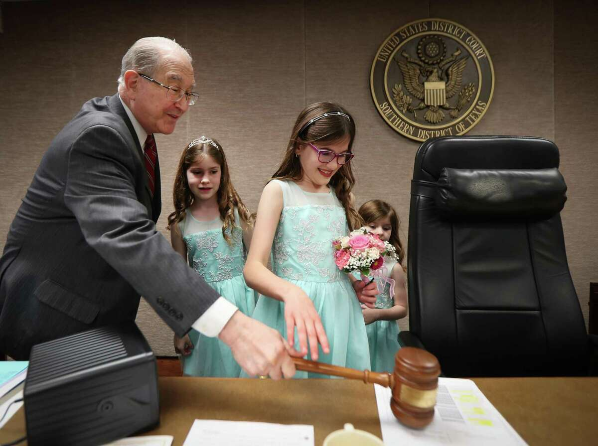 U.S. District Judge David Hittner kept Former U.S. Attorney Ken Magidson's granddaughters Selah (l-r), Macy and Kate George entertained on his bench before marrying Magidson and Laura Kohlmaier Wednesday, Jan. 29, 2020, in Houston.