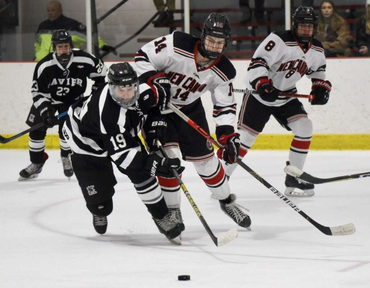 Xavier's Aden Hotchkiss (19) plays the puck in front of New Canaan's Shane Mettler during a boys hockey game at the Darien Ice House on Wednesday. The game finished in a 3-3 tie. Get a full recap at middletownpress.com/sports.