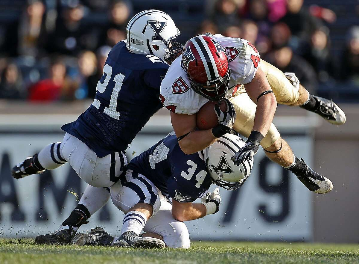 """NEW HAVEN - NOVEMBER 19: Harvard tight end Kyle Juszczyk sails for some yardage after a catch, as yale's Collin Bibb (#21) and John Powers (#34) try to bring him down. Yale hosted Harvard in """"The Game"""" at the Yale Bowl. (Photo by Jim Davis/The Boston Globe via Getty Images)"""